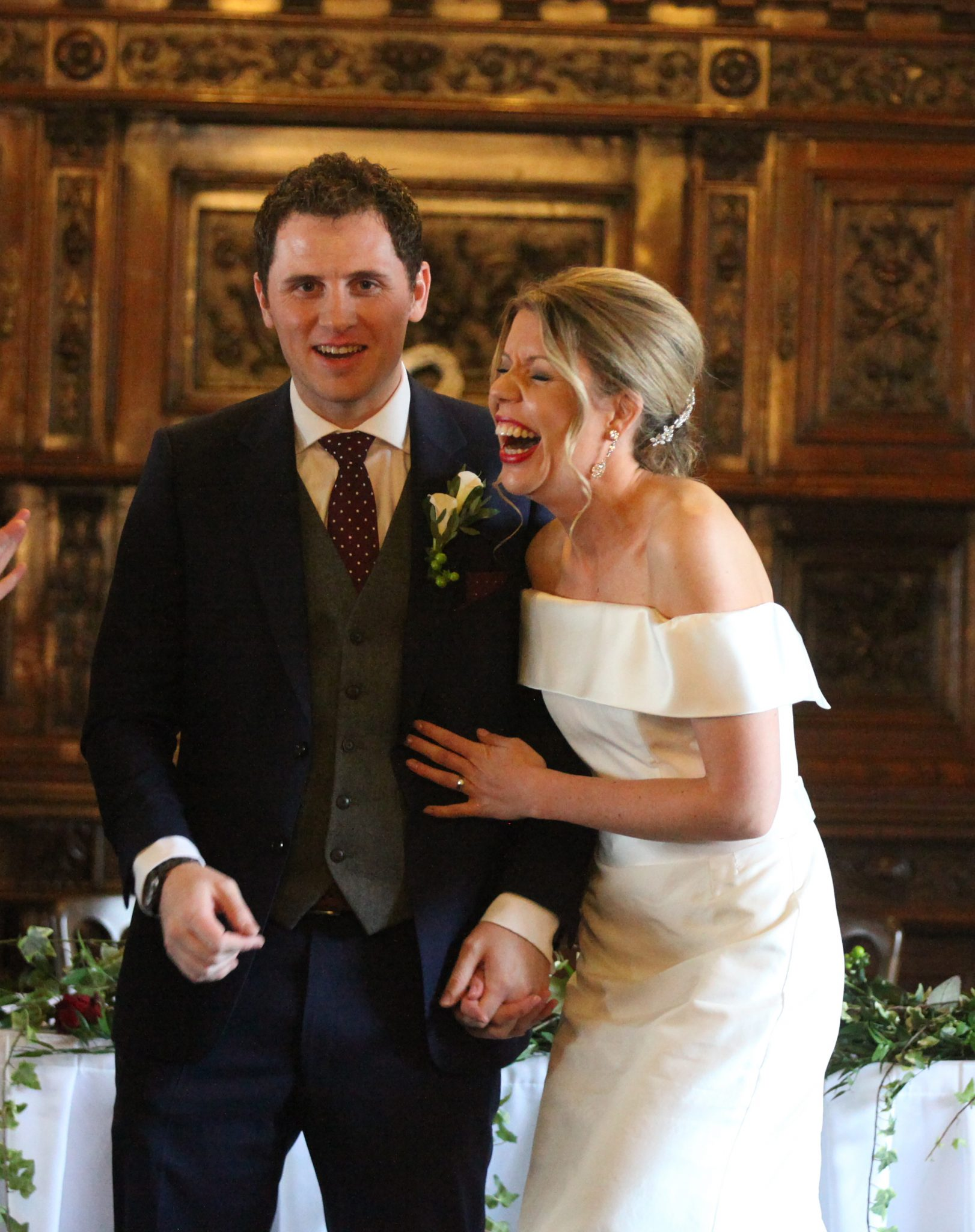 Essendon Country Club bride and groom laugh after being given marriage certficate.