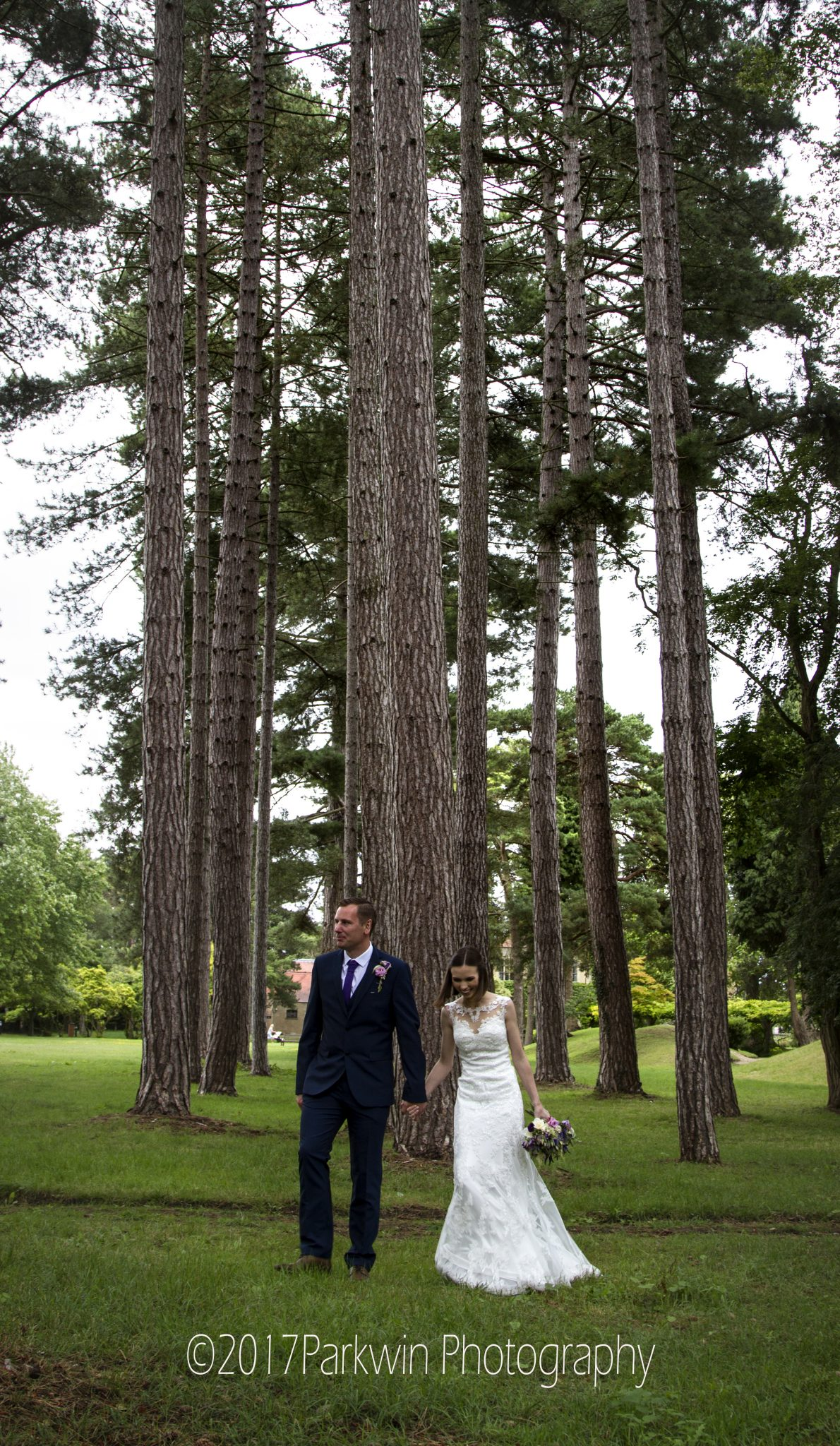 bride and Groom walking hrough trees at Fanhams Hall